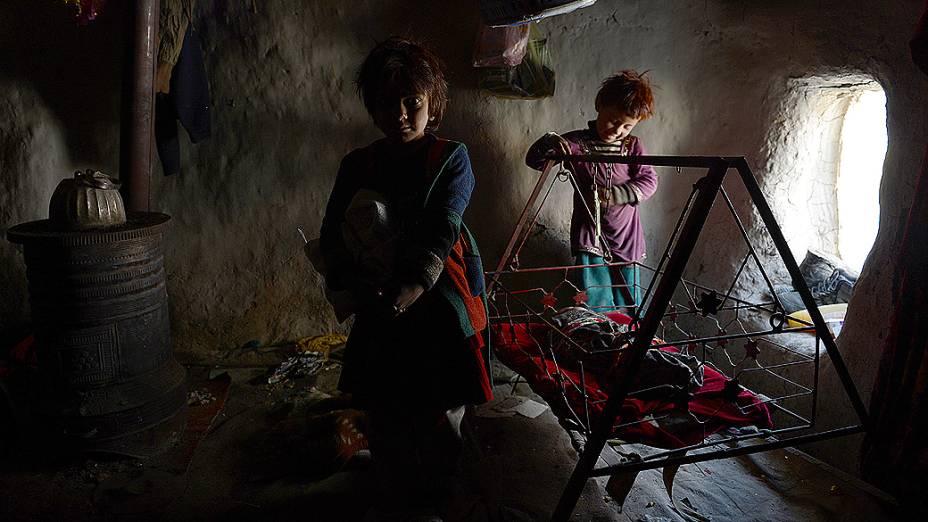Crianças afegãs brincam dentro de um abrigo de barro em um acampamento improvisado em Cabul