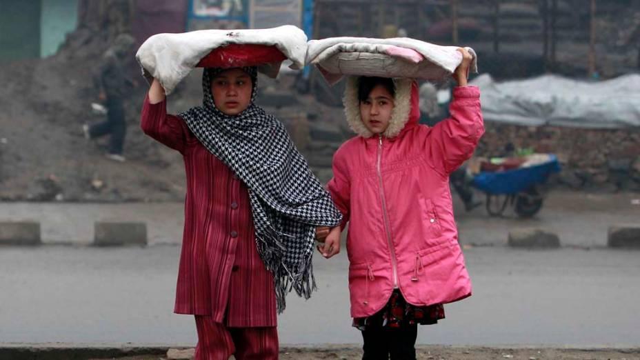 No Afeganistão, meninas carregam pão em uma rua de Cabul