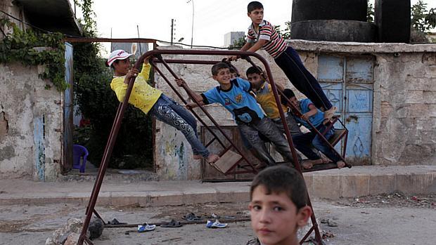 Crianças sírias brincam na cidade destruída de Alepo