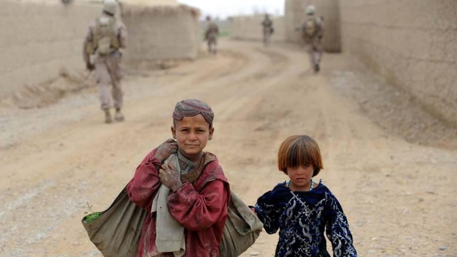 Crianças afegãs caminham nas proximidades do 2° Batalhão da Marinha Americana, na província de Helmand