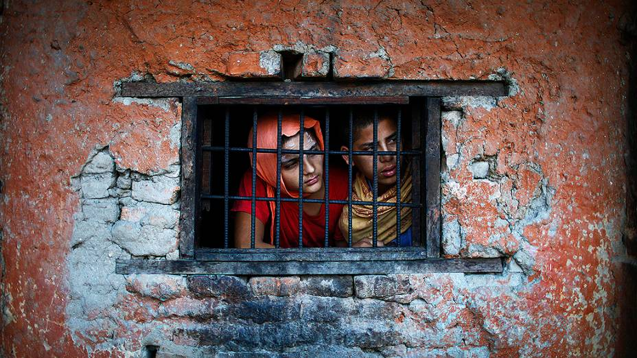 Estudantes de escola hindu olham para fora da janela da sala de aula em Katmandu, no Nepal