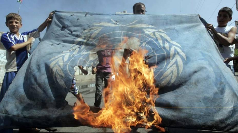 Em Ain al-Helweh, Líbano, palestinos queimam bandeira da UNRWA (agência da ONU que presta assistência aos refugiados palestinos), em protesto contra a degradação dos serviços prestados pela entidade