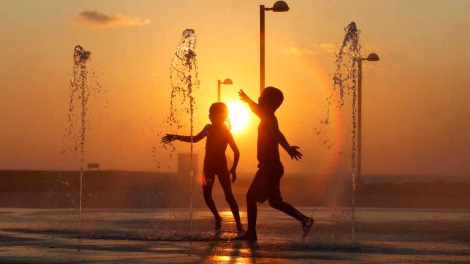 Crianças se refrescam em fonte em Tel Aviv, Israel
