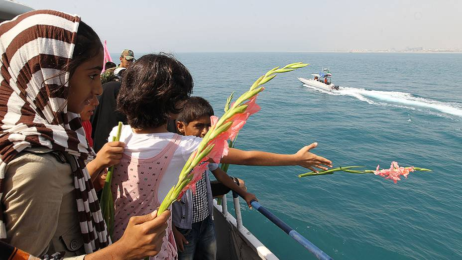 Crianças iranianas jogam flores no mar para celebrar os 24 anos da destruição de por engano de um avião de passageiros do Irã por um míssil americano, matando 290 passageiros