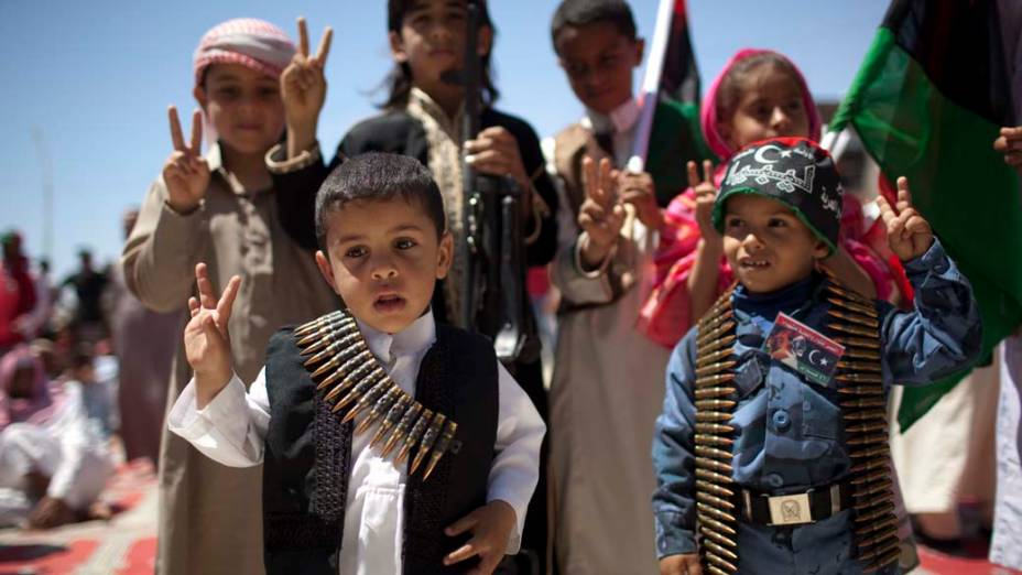 Em Ajdabiya, crianças líbias posam para foto com cintos de munição<br>