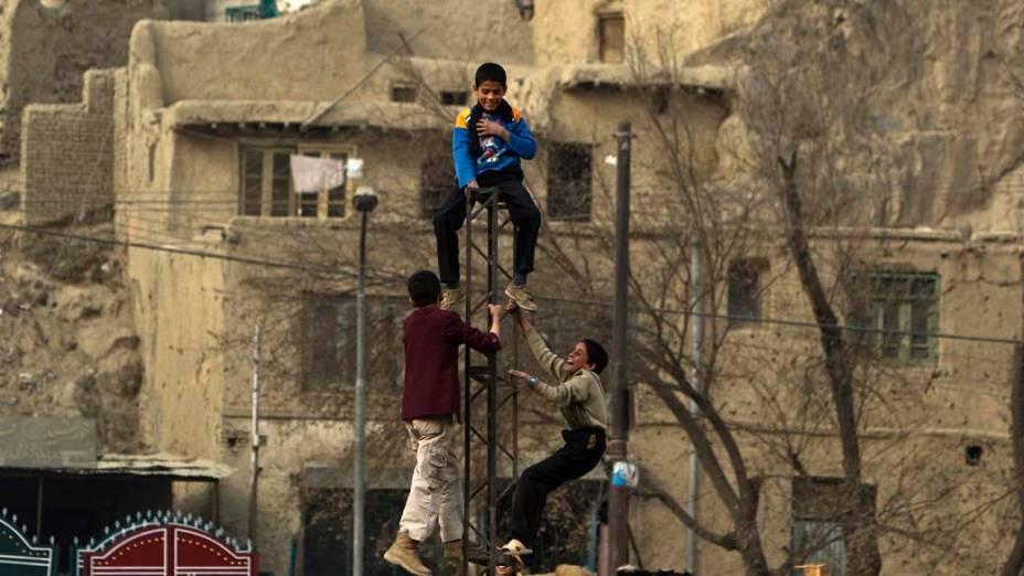 Crianças afegãs brincam em poste elétrico quebrado em Cabul