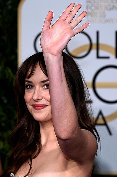 Dakota Johnson, a estrela de 'Cinquenta Tons de Cinza', chega embalada em papel alumínio para a cerimônia do Globo de Ouro)