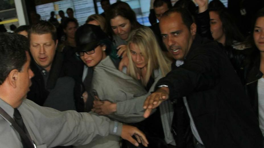 Demi Lovato desembarca em aeroporto de São Paulo escondendo o rosto