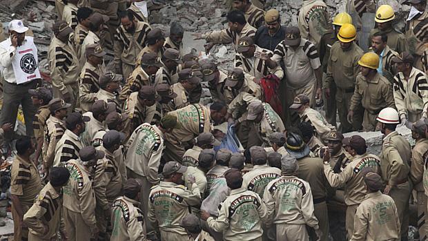 Bombeiros e voluntários tentam retirar uma vítima dos escombros