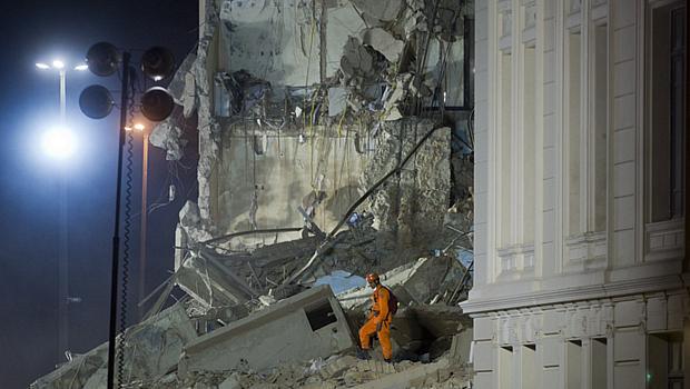 Funcionário da Defesa Civil busca sobreviventes em prédio que desabou na noite desta quarta-feira no centro do Rio de Janeiro