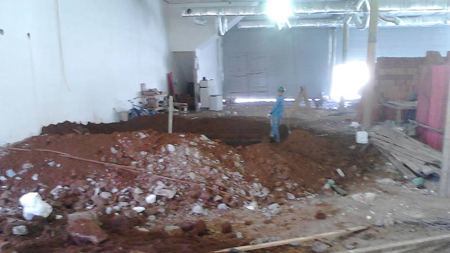 Vista geral do galpão térreo com escavação colada à parede e portas de ferro semiabertas ao fundo