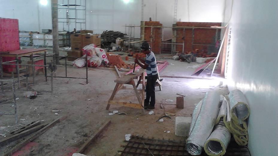 Operário trabalha em mesa na parte posterior do galpão térreo