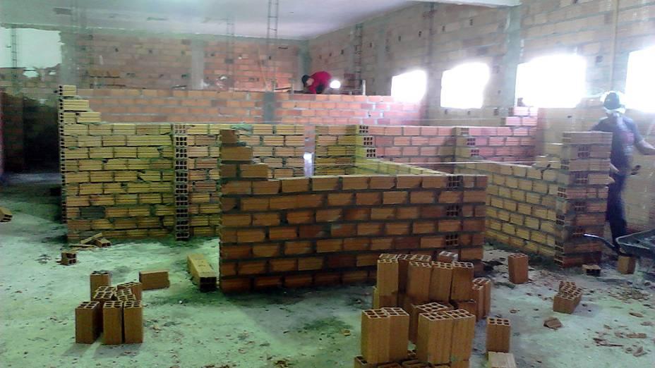 Pedreiros levantam paredes com tijolos armazenados no piso superior