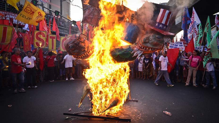 Manifestantes colocam fogo em uma efígie do presidente filipino Benigno Aquino e do presidente dos Estados Unidos, Barack Obama, durante protesto em Manila