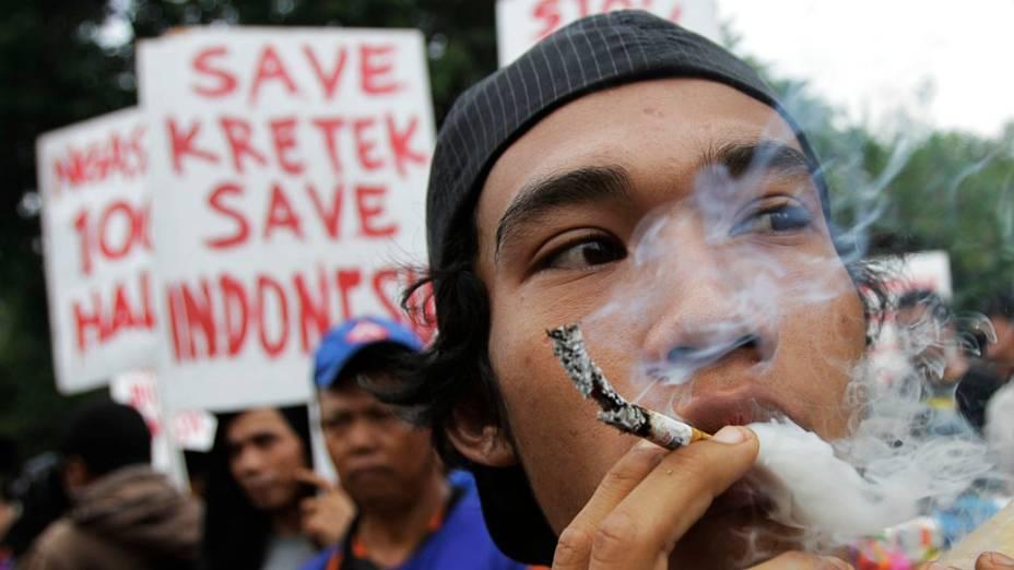 Vendedor de cigarros fuma como protesto durante comício contra o Dia Mundial Sem Tabaco, em Jacarta, Indonésia