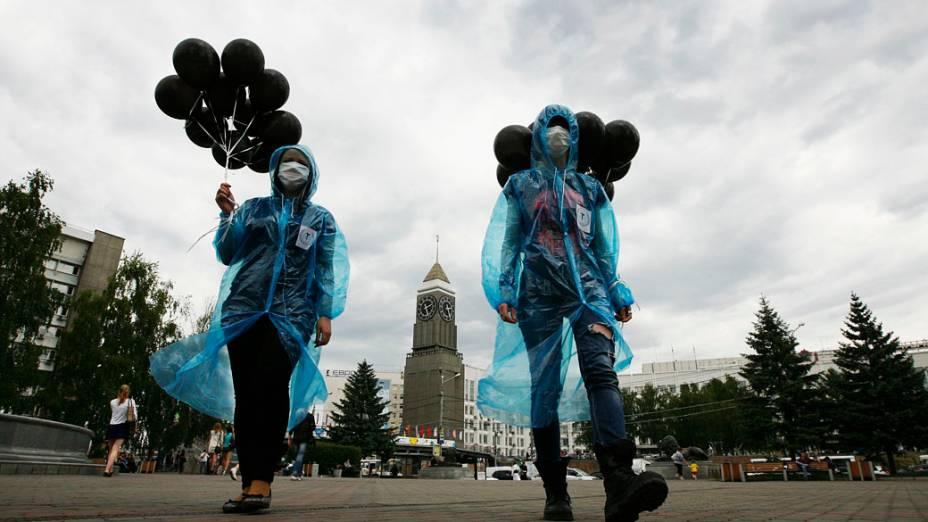 Jovens ativistas, usam máscaras e seguram balões pretos, para participar de um flash mob contra o tabagismo durante o Dia Mundial Sem Tabaco no centro de Krasnoyarsk, Rússia