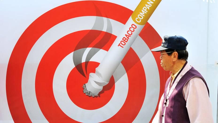Sul-coreano passa por um cartaz durante uma campanha que marca o Dia Mundial sem Tabaco em Seul