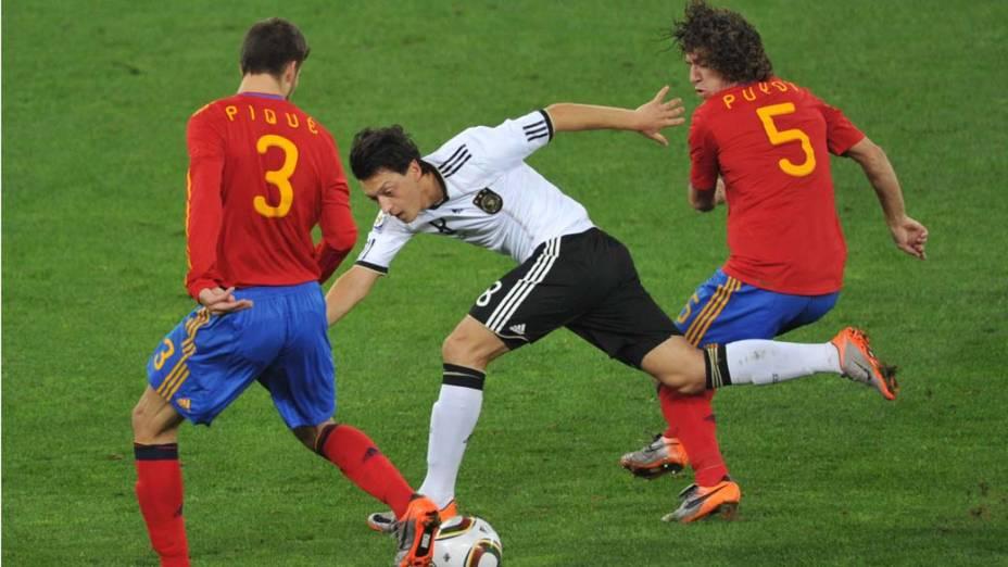 Mesut Oezil tenta sair da defesa espanhola durante a partida Alemanha e Espanha pela Semifinal da Copa da África do Sul