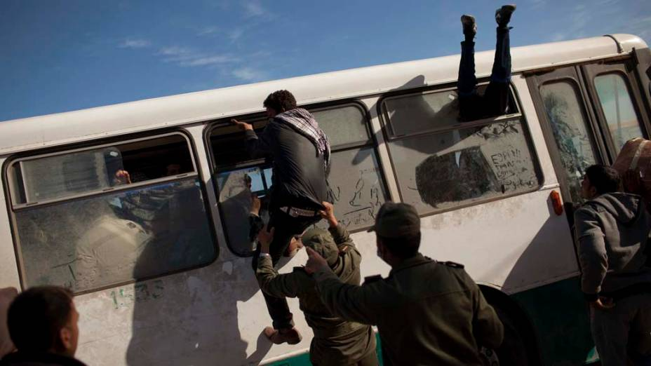 Egípcios tentam embarcar em ônibus na cidade de Ras Jedir, na fronteira entre a Tunísia e a Líbia