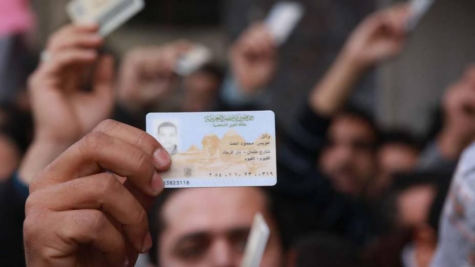 Manifestantes seguram suas identidades para entrarem na praça Tahrir no Cairo, Egito. As autoridades fecharam todas as estradas e transportes públicos para o Cairo, onde milhares de pessoas estão convergindo para exigir a deposição do presidente egípcio, Hosni Mubarak