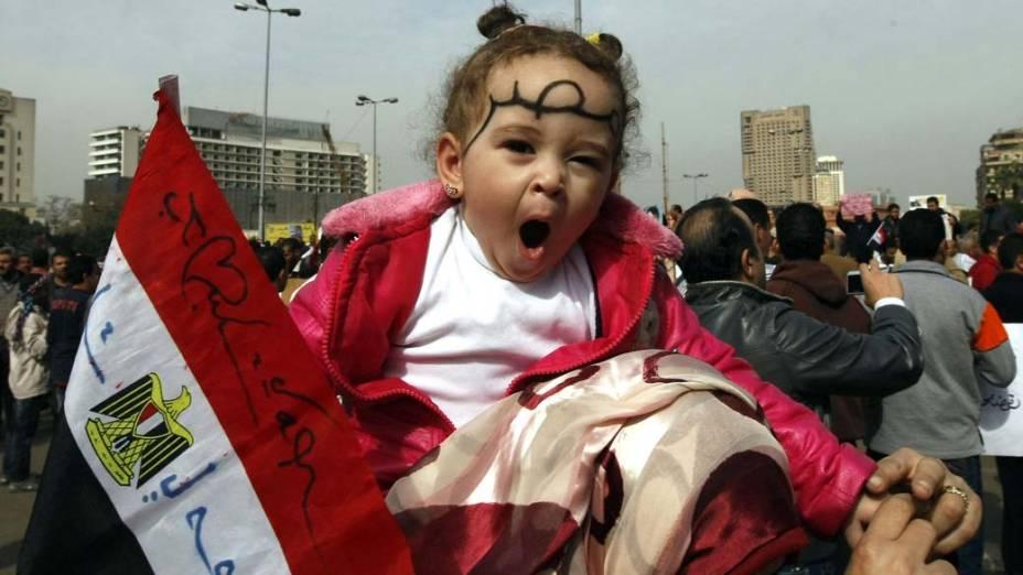 Mulher carrega a filha em seus ombros durante manifestação na praça Tahrir, no Cairo, Egito