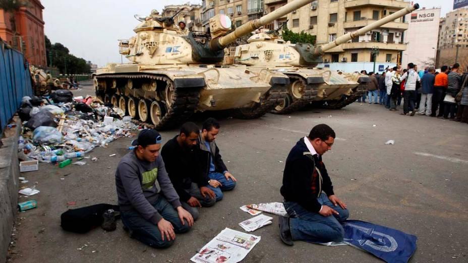 Manifestantes rezam na frente dos tanques do exército durante protesto na praça Tahrir, no Cairo, Egito
