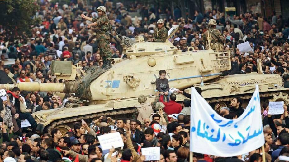 Manifestantes ao redor de um tanque do exército durante protesto no Cairo, Egito