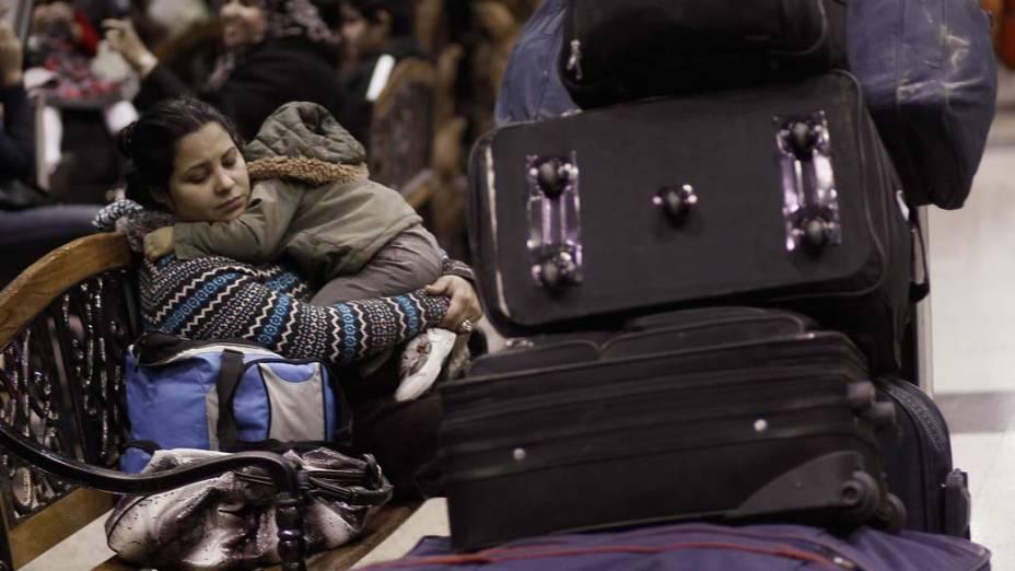 No Aeroporto Internacional do Cairo, mulher aguarda com o seu filho um voo para sair do Egito