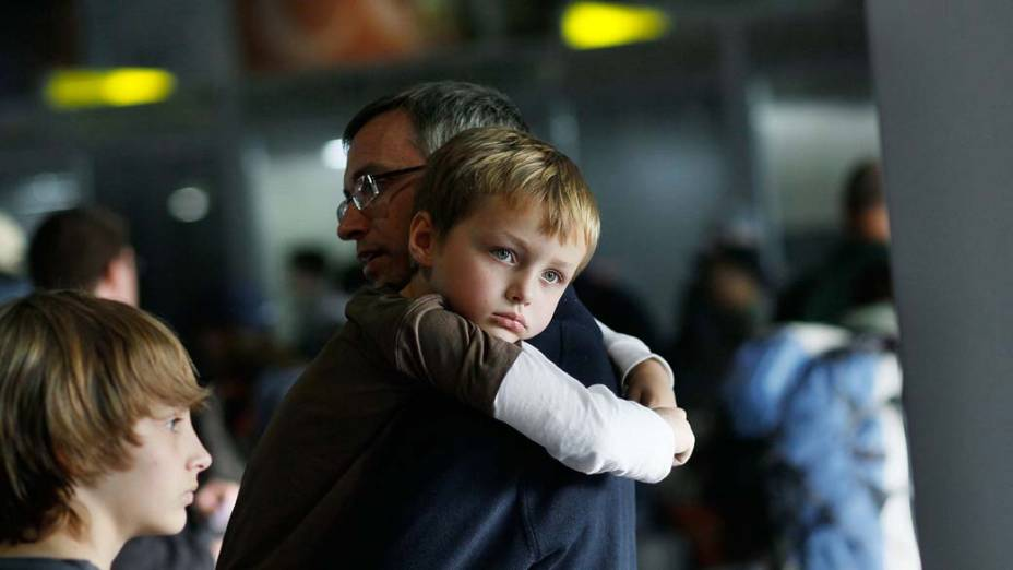 No Aeroporto Internacional do Cairo, Liam Johnson, 6 anos, é carregado por seu pai, Peter Johnson, enquanto aguardam um voo para sair do Egito