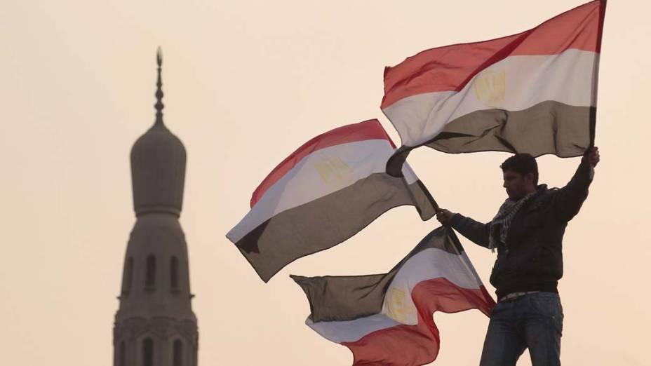 No Cairo, jovem levanta bandeiras do Egito durante protesto na praça Tahrir