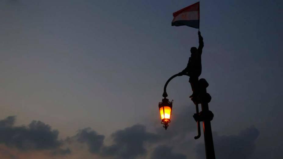 Manifestante com a bandeira egípcia na praça Tahrir, no Cairo, Egito