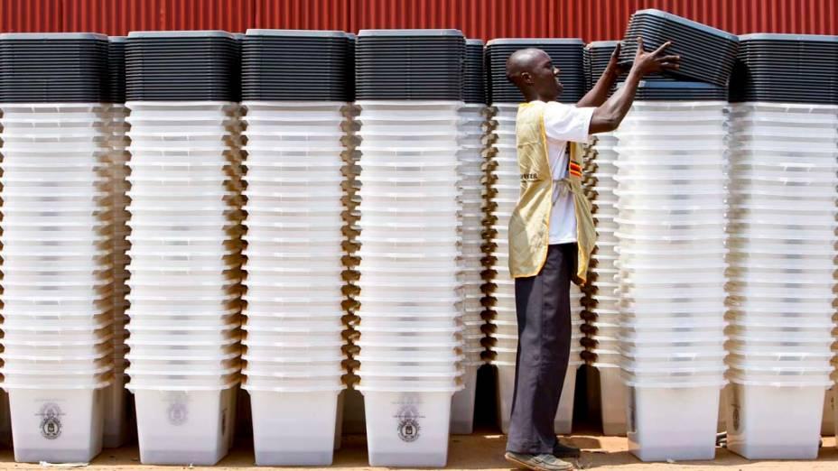Homem organiza urnas que serão usadas nas eleições multipartidárias de Uganda