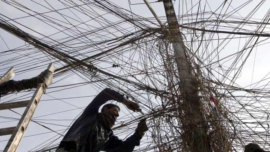 Eletricista revisa cabos de energia no bairro de Karrada, Bagdá
