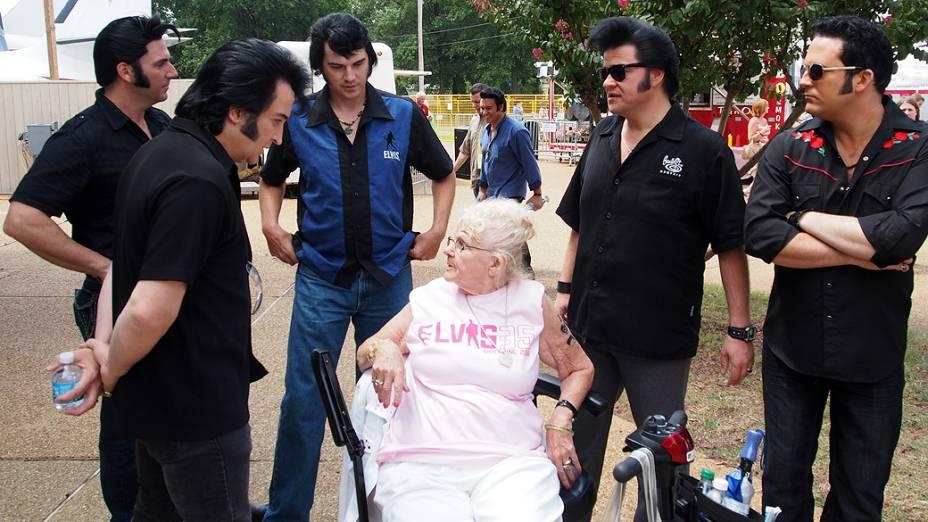 Sósias de Elvis Presley em volta de uma fã do cantor em Gracelando durante a Elvis Week