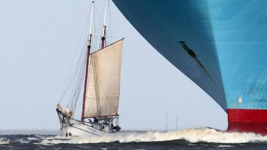 """No Mar do Norte, o veleiro """"Flying Dutchman"""" e o navio de carga """"Elly Maersk"""". Acontece até domingo em Bremerhaven, na Alemanha, um encontro naval no qual participam cerca de 200 embarcações"""
