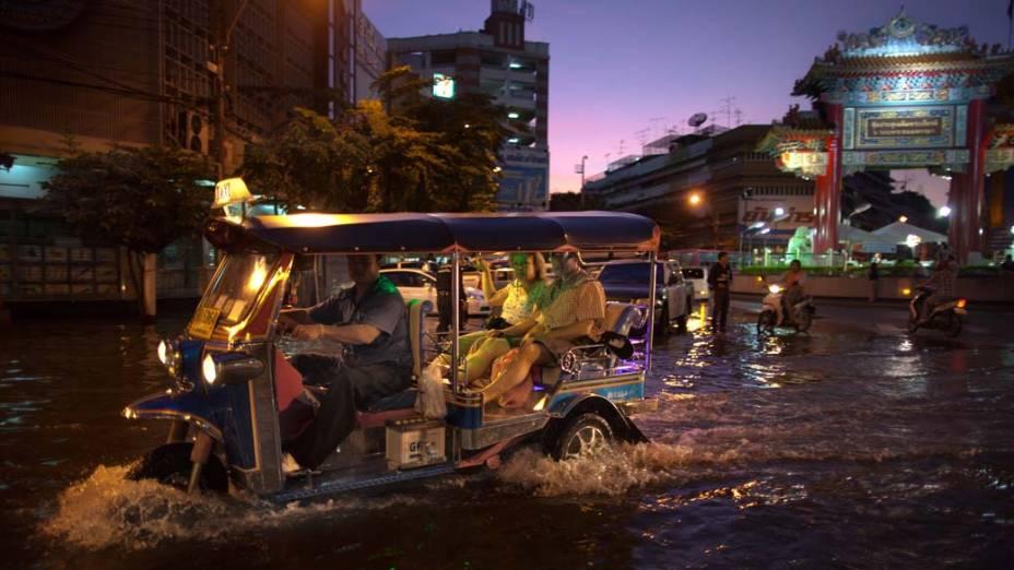 Motorista de Tuk Tuk dirige por ruas alagadas de Bangcoc, na Tailândia
