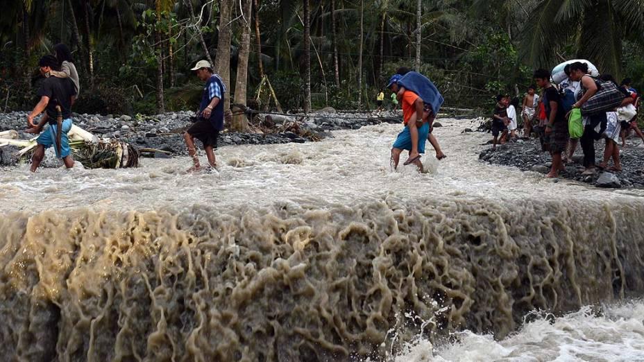 Moradores atravessam estrada destruída pelo tufão Bopha, na aldeia de Andap, Filipinas