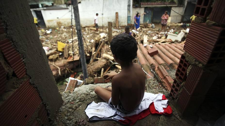 Menino observa rua repleta de entulhos após a tempestade que atingiu o bairro do Café Torrado, em Xerém, Duque de Caxias