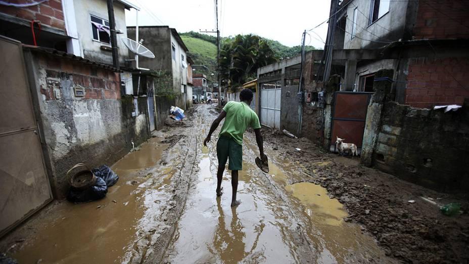 Homem caminha em rua repleta de entulhos após a tempestade que atingiu o bairro do Café Torrado, em Xerém, Duque de Caxias
