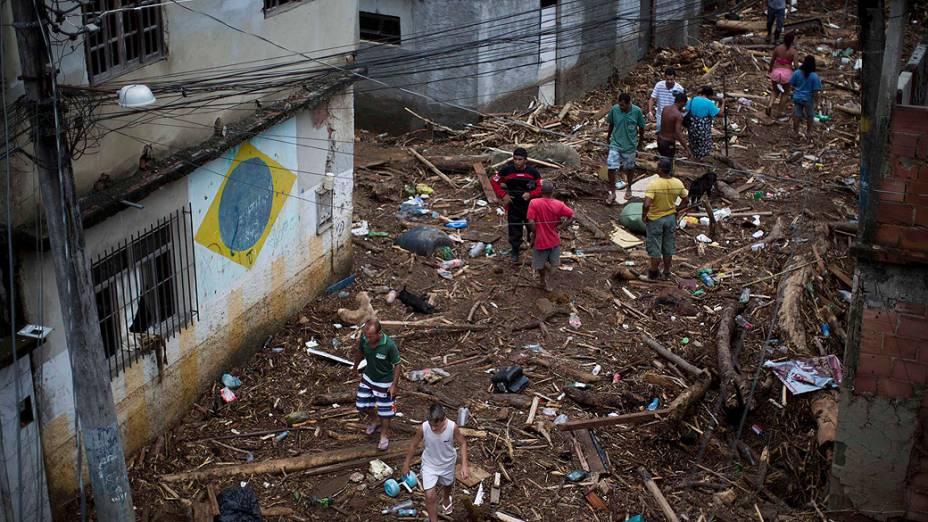 Pessoas caminham em rua repleta de entulhos após a tempestade que atingiu o bairro do Café Torrado, em Xerém, Duque de Caxias