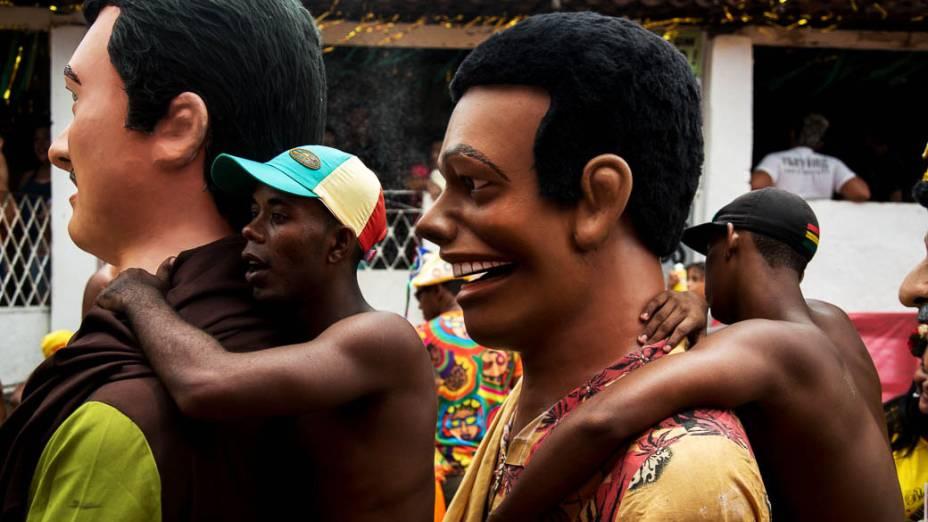Homens se penduram em Bonecos Gigantes em Olinda