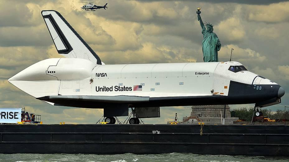 Barco leva o ônibus espacial Enterprise pelo rio Hudson, em Nova York (EUA). O destino da espaçonave é o museu Intrepid Sea
