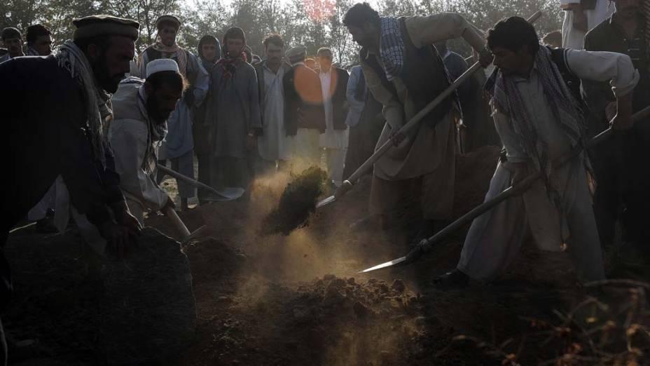 Afegãos enterram vítimas de explosão de um tanque de combustível perto da base aérea de Bagram, no Afeganistão