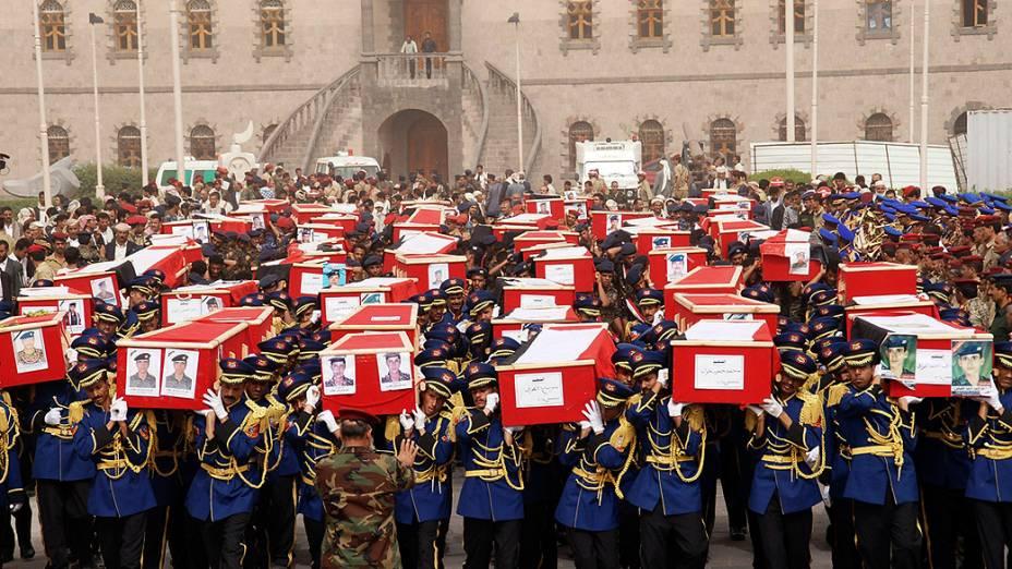 Guarda de honra iemenita carrega caixões dos soldados mortos em atentado suicida, durante procissão funerária em Sanaa. Pelo menos 70 pessoas morreram no atentado