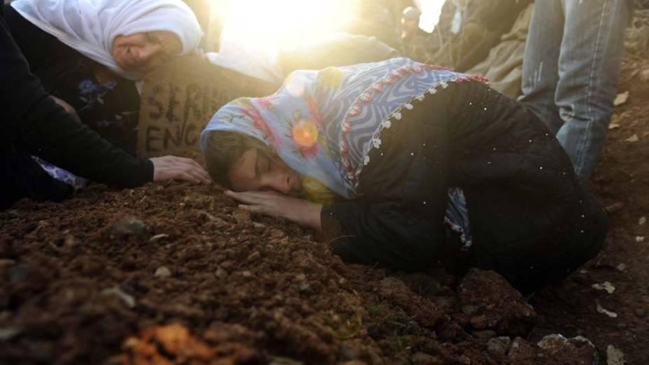 Mulheres choram durante enterro das vítimas do ataque aéreo turco contra curdos no cemitério de Gulyazi, Turquia