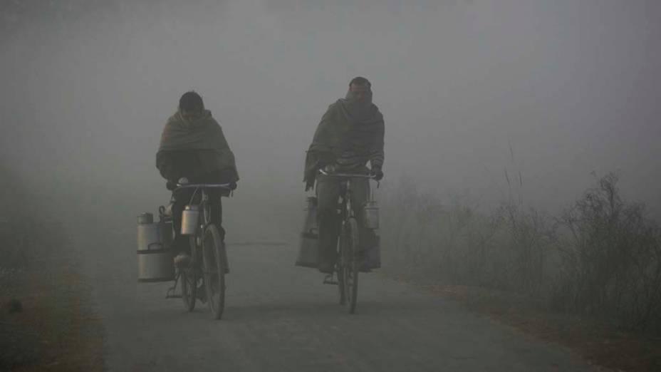 Entregadores de leite passam por neblina na cidade de Jammu, Índia