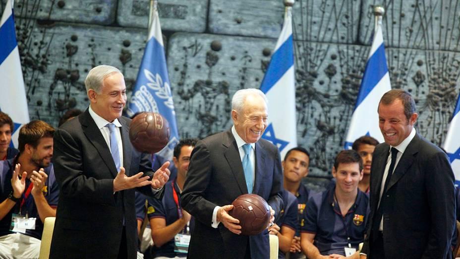 O presidente de Israel, Shimon Peres (C), e o primeiro-ministro, Benjamin Netanyahu (E), recebem uma bola do FC Barcelona do presidente do clube, Sandro Rosell, durante recepção na residência de Peres, em Jerusalém