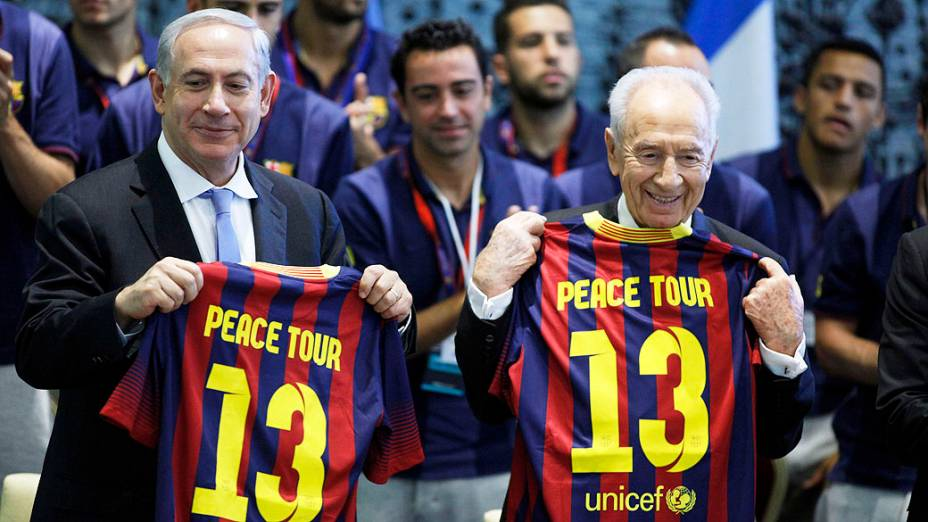 O presidente de Israel, Shimon Peres (D), e o primeiro-ministro, Benjamin Netanyahu, com camisas do Barcelona durante uma recepção na residência de Peres, em Jerusalém