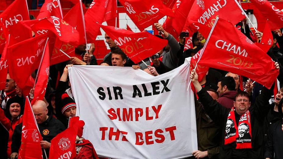 Torcedores estendem bandeiras em homenagem aAlex Ferguson, que assume o comando para o seu último jogo em casa antes de se aposentar, no estádio Old Trafford, em Manchester