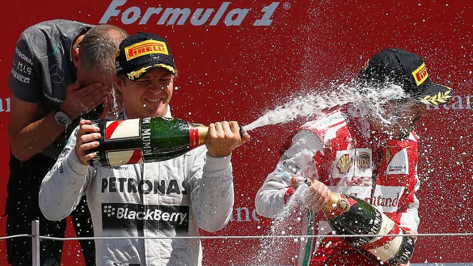Nico Rosberg da Alemanha comemora após vencer o Grande Prêmio da Inglaterra com o terceiro colocado, Fernando Alonso, da Espanha, no circuito de corrida de Silverstone